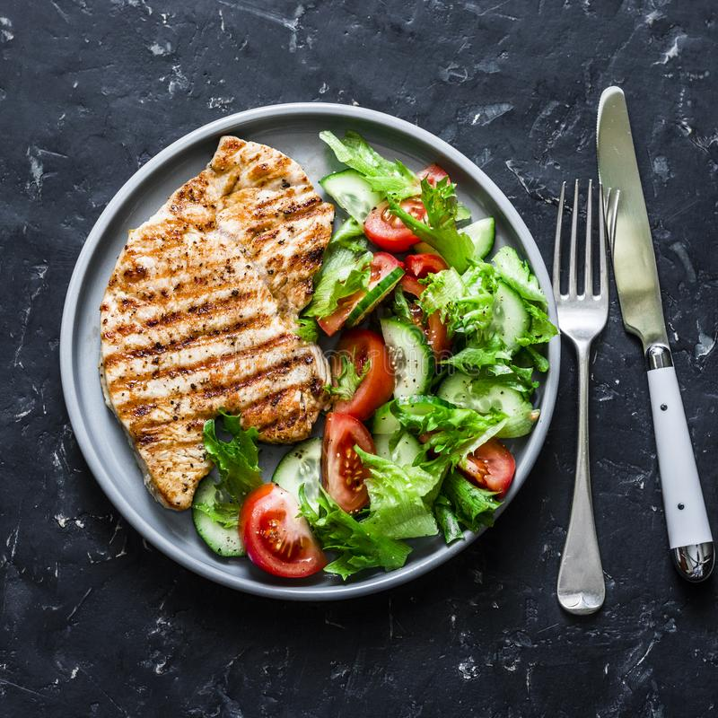 Grilled turkey  and tomatoes, cucumbers salad on a dark background, top view. Healthy food diet concept royalty free stock images