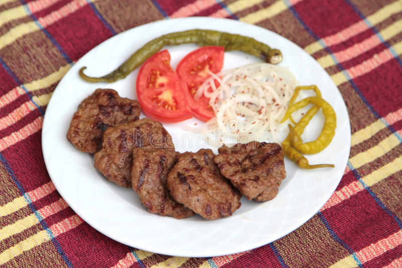 Grilled Turkish meatballs, ( Kofte ), on white plate stock images