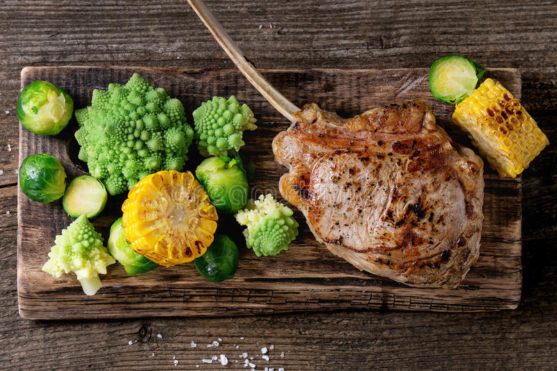 Grilled veal steak with vegetables. Grilled veal tomahawk steak with vegetables brussels sprouts, romanesco and corn cobs served on wooden serving chopping board stock photos