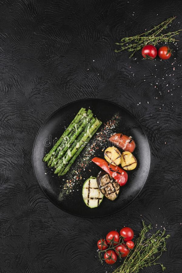 Grilled vegetables on a black plate. Asparagus, bell pepper, zucchini, eggplant, potatoes and tomatoes baked on the fire royalty free stock image