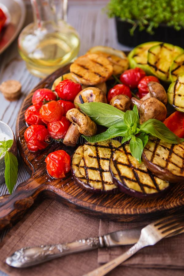 Grilled vegetables on cutting board on wooden background. Grilled vegetables colorful bell pepper, tomatoes, onion, zucchini, royalty free stock photo