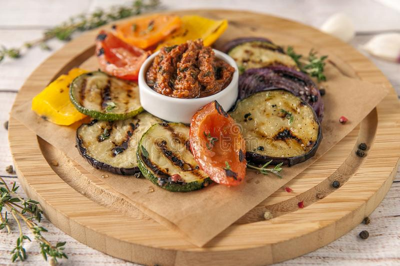 Grilled vegetables with fresh spicy greens and pesto sauce stock image