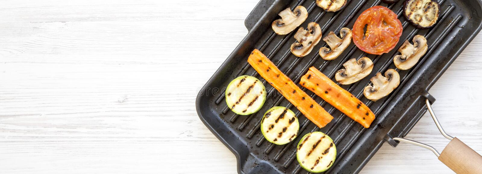 Grilled vegetables in a grilling pan over white wooden background, top view. From above, overhead. Space for text.  royalty free stock photography