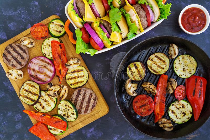 Grilled vegetables and handmade burger. Zucchini, eggplant, mushrooms, pepper on the grill. Top view stock photo