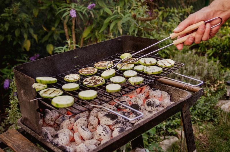 Grilled vegetables. The man turns the vegetables on the grill to avoid scratching. There is a family dinner. The family met at the weekend and spend their free royalty free stock image