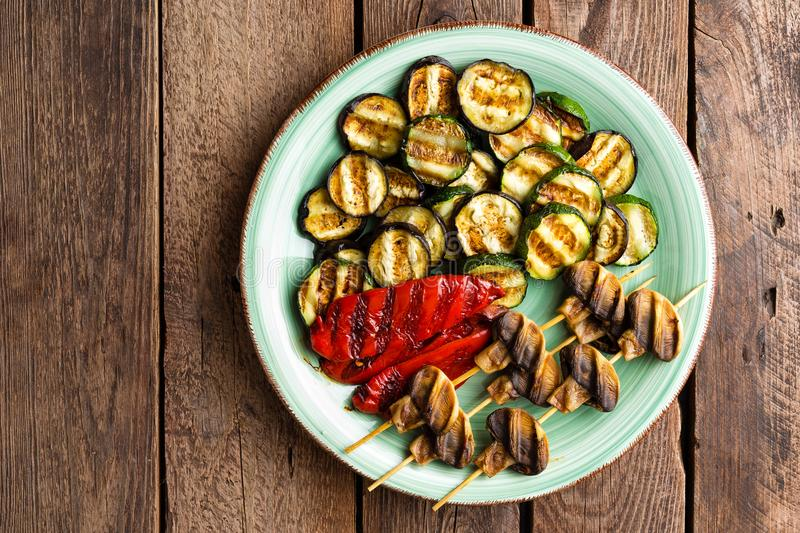 Grilled vegetables and mushrooms. Grilled zucchini, eggplant, sweet pepper and mushrooms on plate royalty free stock images