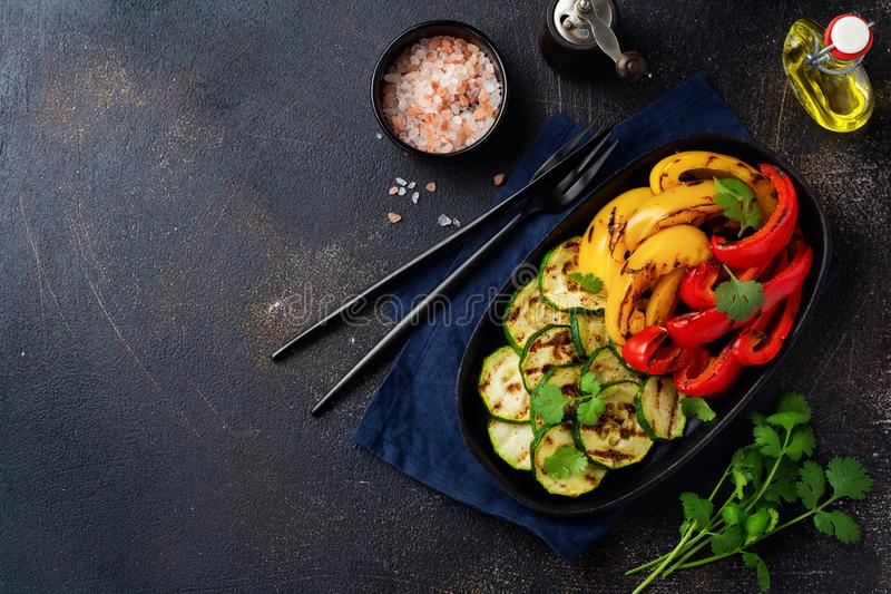 Grilled vegetables pieces of zucchini, red and yellow pepper and bouquet of cilantro on plate, salad on bbq grill rack over charco. Al. Top view. Barbecue royalty free stock images