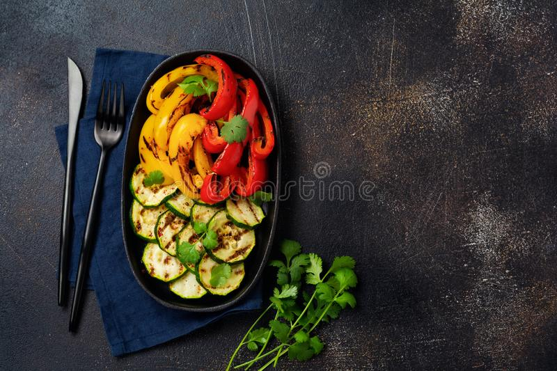 Grilled vegetables pieces of zucchini, red and yellow pepper and bouquet of cilantro on plate, salad on bbq grill rack over charco. Al. Top view. Barbecue stock photos