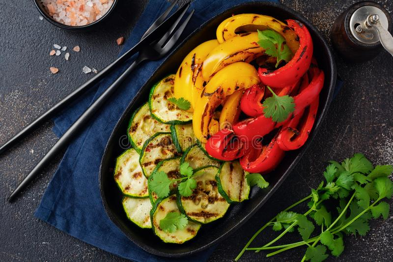 Grilled vegetables pieces of zucchini, red and yellow pepper and bouquet of cilantro on plate, salad on bbq grill rack over charco. Al. Top view. Barbecue royalty free stock image