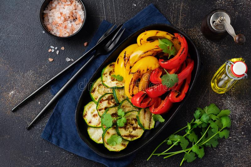 Grilled vegetables pieces of zucchini, red and yellow pepper and bouquet of cilantro on plate, salad on bbq grill rack over charco. Al. Top view. Barbecue stock photo