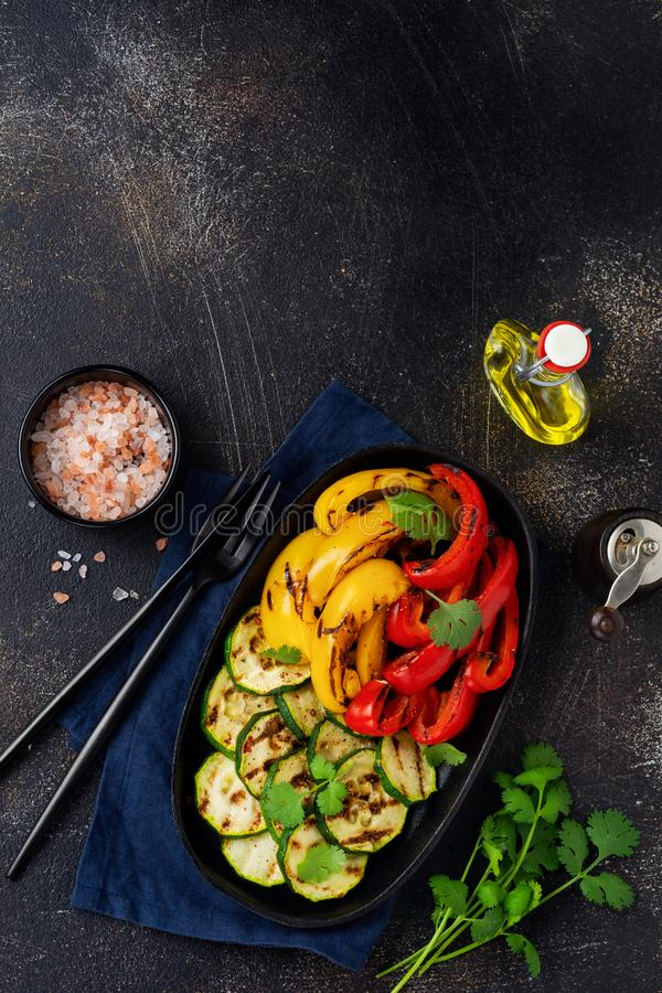 Grilled vegetables pieces of zucchini, red and yellow pepper and bouquet of cilantro on plate, salad on bbq grill rack over charco. Al. Top view. Barbecue stock photography