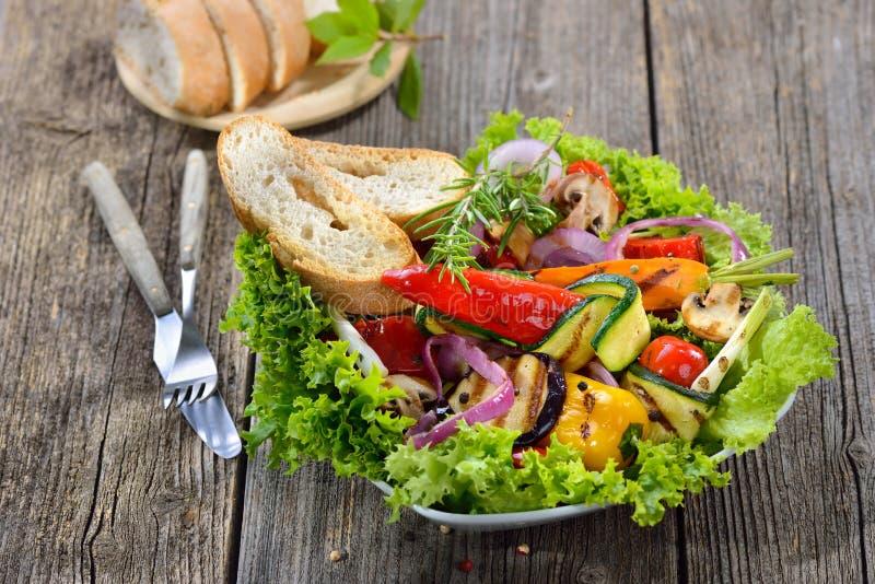 Grilled vegetables on salad stock images