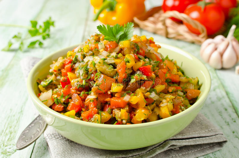 Grilled vegetables salad with yellow and red bell pepper, eggplant, onions, peppers, cilantro and tomato stock image
