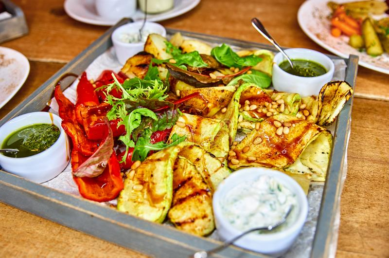 Grilled vegetables and sauces on a tray, on a wooden background royalty free stock photo