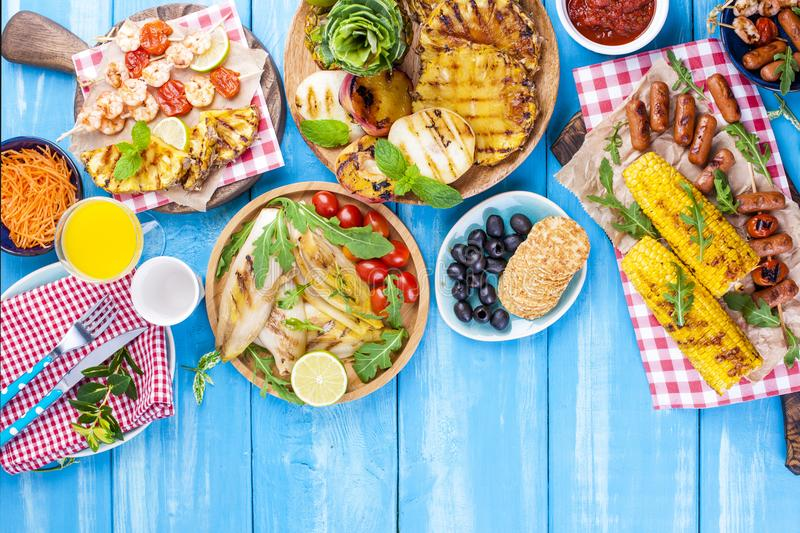 Grilled vegetables, shrimp, fruit on a wooden plate and sausages, juice and salad on a blue background. Summer dinner. Free space stock image