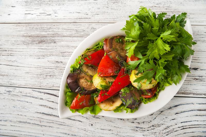 Grilled vegetables in a white plate close-up. Snack from baked vegetables with Provencal herbs to copy space.  stock photography