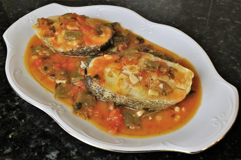 Grilled white fish in sauce with vegetables royalty free stock photo
