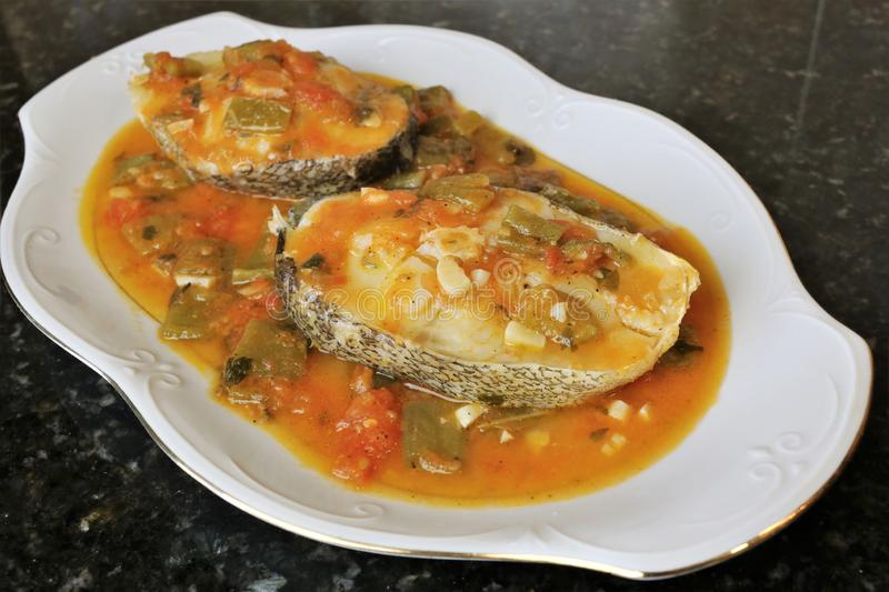 Grilled white fish in sauce with vegetables royalty free stock photography