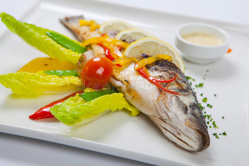 Grilled whole fish decorated with leaves of lettuce and cherry tomato, served with garlic sauce. Fried whole fish royalty free stock image