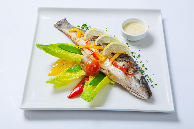 Grilled whole fish decorated with leaves of lettuce and cherry tomato, served with garlic sauce. Fried whole fish stock photo
