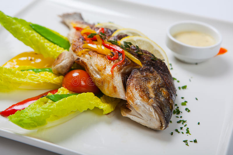 Grilled whole fish decorated with leaves of lettuce and cherry tomato, served with garlic sauce. Fried whole fish royalty free stock images