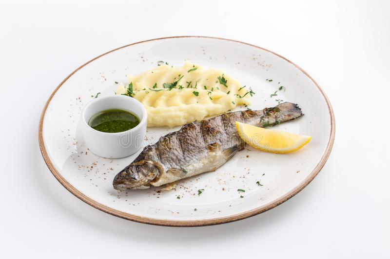Grilled whole fish with mashed potato, lemon and soy sauce isolated on white background stock images