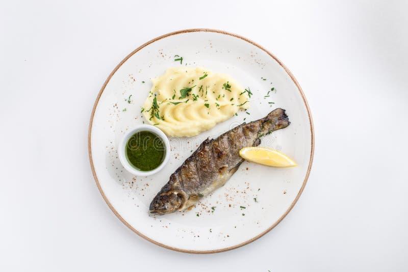 Grilled whole fish with mashed potato, lemon and soy sauce isolated on white background royalty free stock image