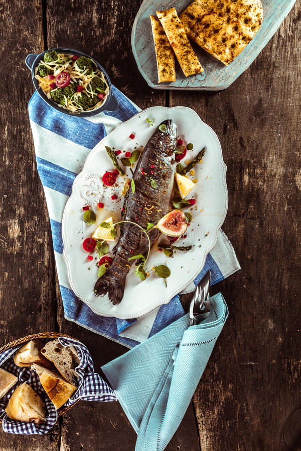 Grilled Whole Fish and Meal on Wooden Table stock image