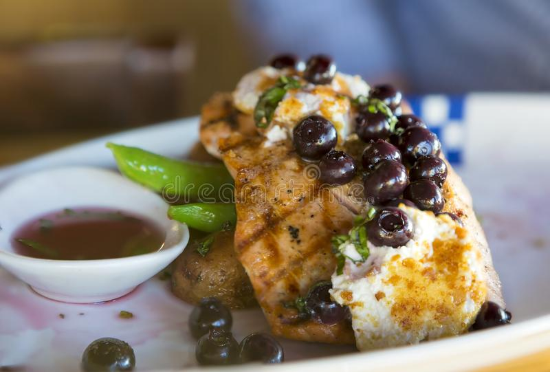 Grilled Wild Salmon with Blueberries and Goat Cheese. Grilled Wild Alaskan Salmon with blueberries goat cheese over potatoes green beans dinner plate closeup royalty free stock photography