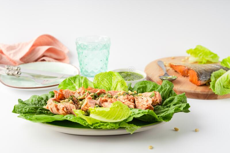 Grilled wild salmon and lettuce dish with green pesto, linen, cutlery, plate, glass of water on white background. Closeup view, horizontal orientation, fish stock photos