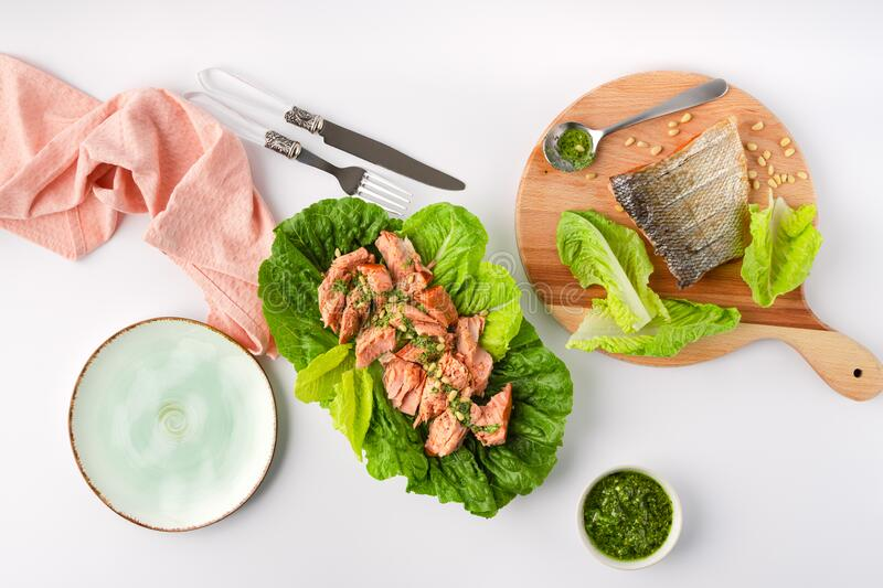 Grilled wild salmon and lettuce dish with green pesto, linen, cutlery, plate on white background, top view. Grilled wild salmon and lettuce dish with green pesto stock image