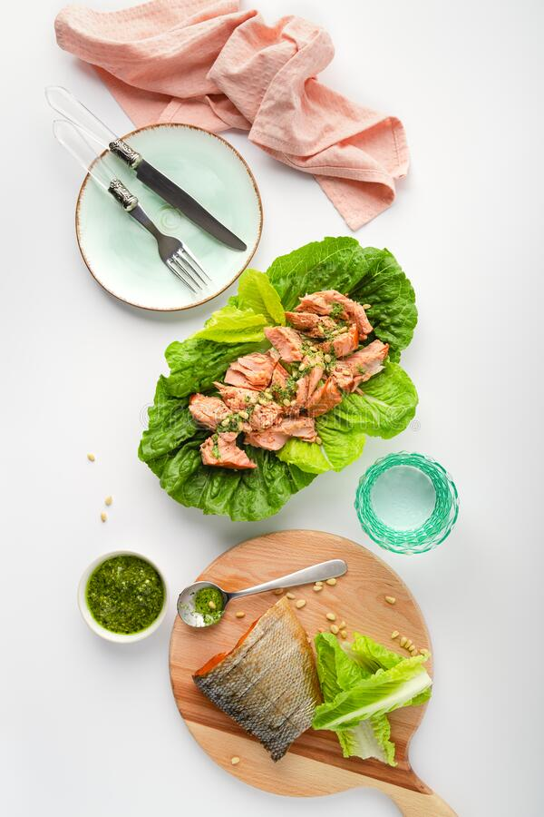 Grilled wild salmon and lettuce dish with green pesto, top view, vertical banner. Grilled wild salmon and lettuce dish with green pesto, linen, cutlery. Top view stock photography