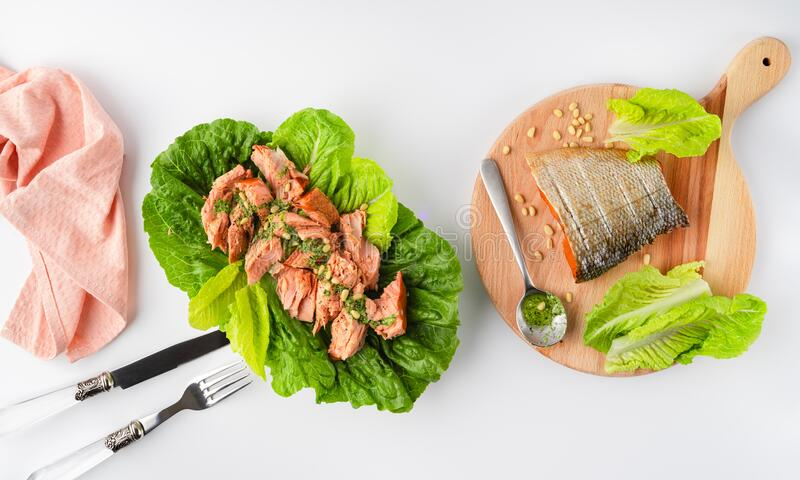 Grilled wild salmon and lettuce dish, linen, cutlery, fish on wooden board on white background, top view. Grilled wild salmon and lettuce dish, linen, cutlery stock photos