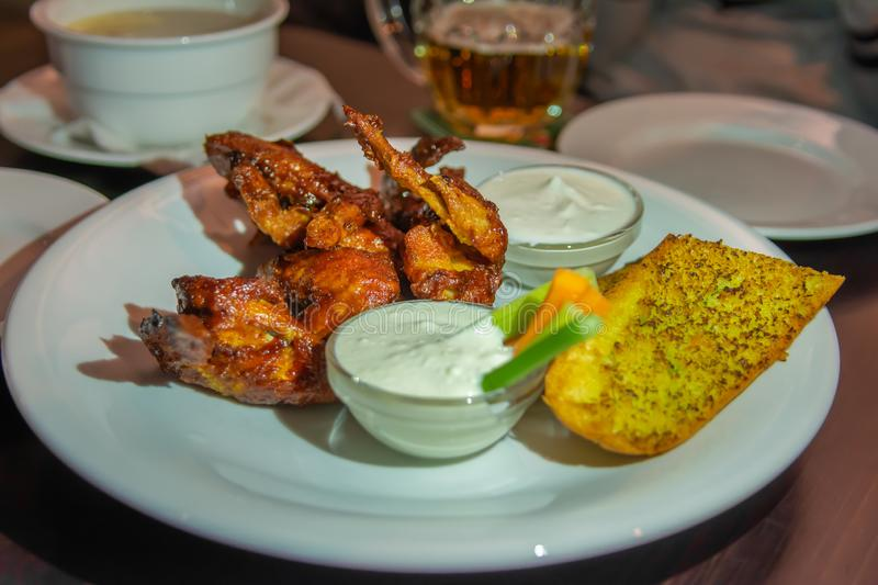 Grilled wings on the grill with sauce, leek and croutons. Beer in the background. Beer snack royalty free stock image