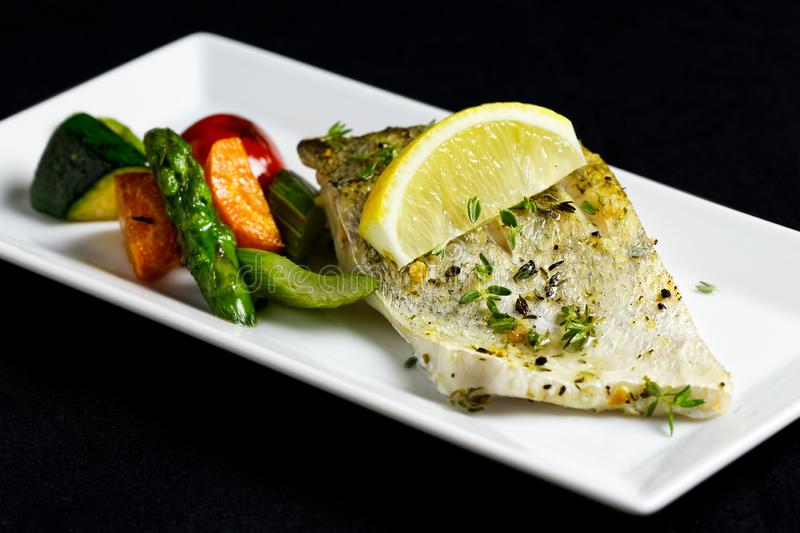 Grilled zander fillet with mixed grilled vegetables on white rectangular plate. Black background royalty free stock photo