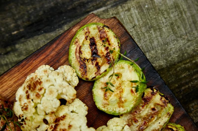 Grilled zucchini and cauliflower vegetable on wooden background royalty free stock images