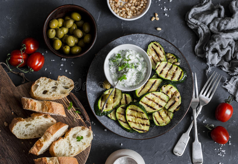 Grilled zucchini, olives, tomatoes, ciabatta - simple snack or appetizer. Mediterranean style food. On a dark background, top view royalty free stock photography