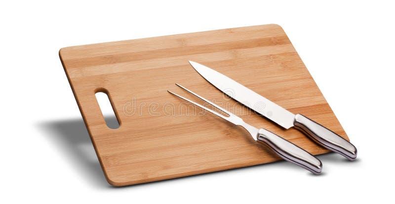 Grillen Sie Ausrüstung mit Holz, um das Fleisch, Messer und lange Gabel zu schneiden, lokalisiert im weißen Hintergrund stockbild