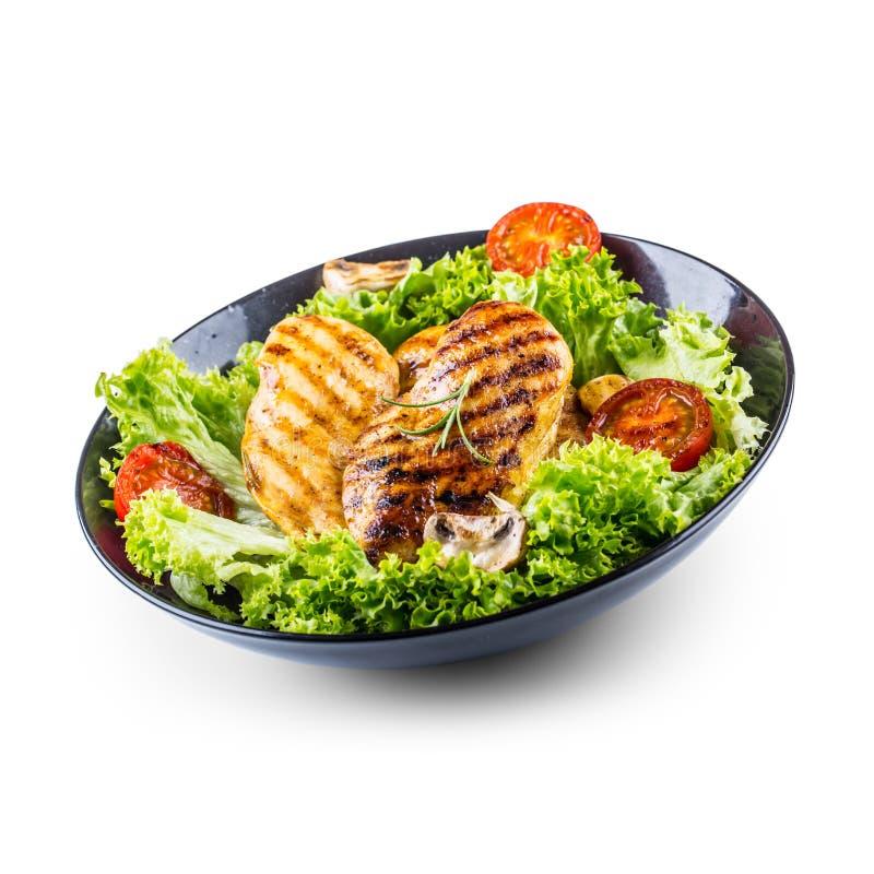 Grillen Sie die Hühnerbrust, die gebraten wird und grillen Sie Hühnerbrust mit den Kopfsalatsalattomaten und -pilzen, die auf Wei stockfotografie