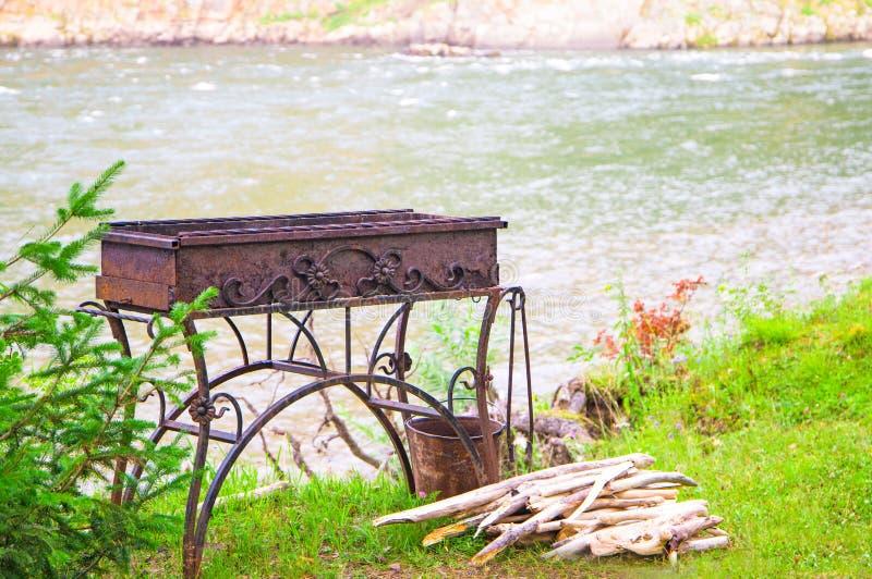 Grillen Sie Messingarbeiter mit Brennholz auf Partei BBQ im Freien nahe dem Fluss stockfotos