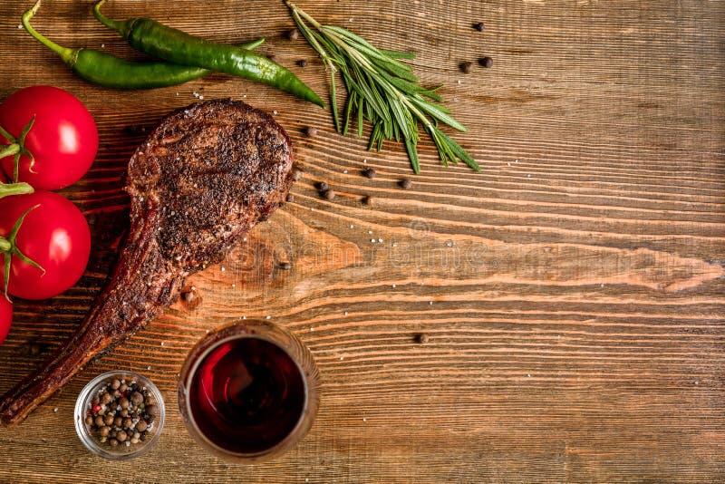 Grillen Sie trockene gealterte Rippe des Rindfleisches mit Gemüse und Glas der Rotweinnahaufnahme auf hölzernem Hintergrund stockbild