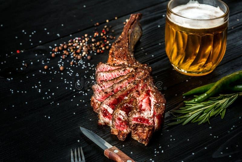 Grillen Sie trockene gealterte Rippe des Rindfleisches mit Gewürz, Gemüse und einem Glas der Nahaufnahme des hellen Bieres auf sc stockfotografie