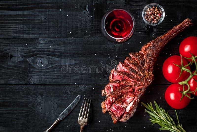 Grillen Sie trockene gealterte Rippe des Rindfleisches mit Gewürz, Gemüse und Glas der Rotweinnahaufnahme auf schwarzem hölzernem stockbild