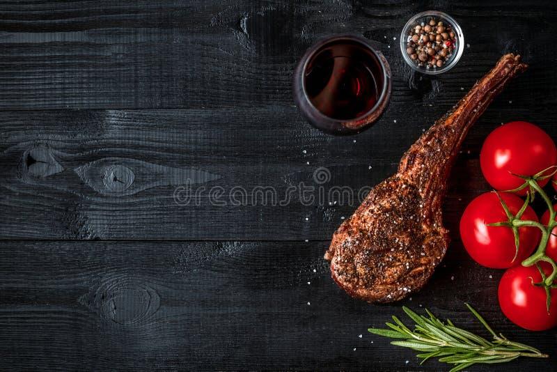 Grillen Sie trockene gealterte Rippe des Rindfleisches mit Gewürz, Gemüse und Glas der Rotweinnahaufnahme auf schwarzem hölzernem lizenzfreies stockfoto