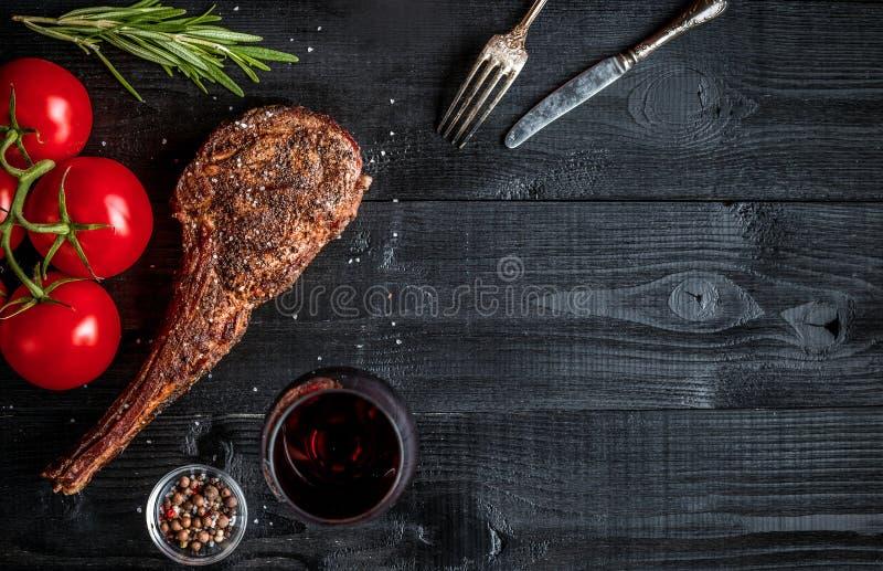 Grillen Sie trockene gealterte Rippe des Rindfleisches mit Gewürz, Gemüse und Glas der Rotweinnahaufnahme auf schwarzem hölzernem stockbilder