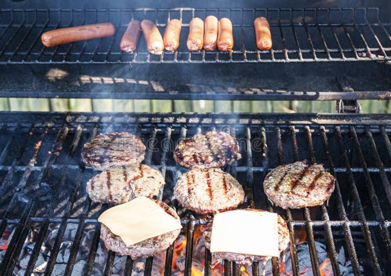 Grillen von Würstchen und von Hamburgern stockbild