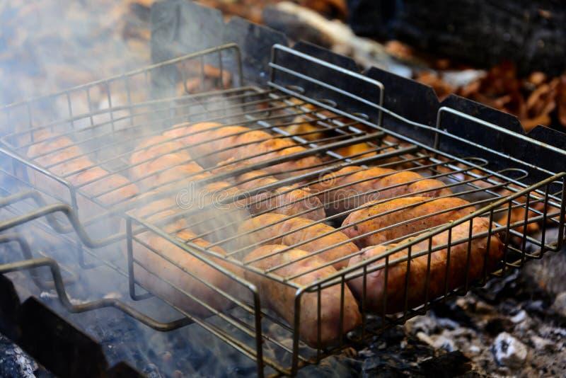 Grillen von Würsten auf Grillgrill BBQ in der Herbstwaldnahaufnahme Weicher Fokus lizenzfreie stockbilder