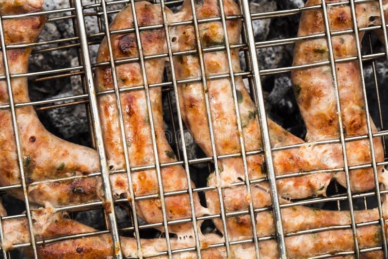 Grillen von Würsten auf Grillgrillhintergrund lizenzfreies stockbild