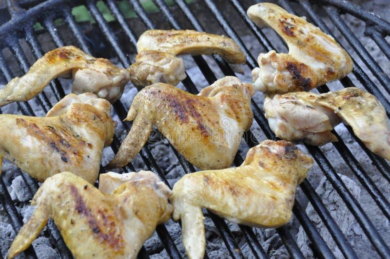 Grillen von würzigen Hühnerflügeln auf Grillgrill stockfotografie
