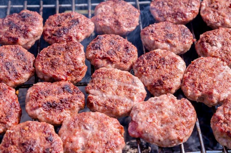 Griller des boulettes de viande sur le gril Cuisson du barbecue avec le charbon de bois dans le jardin image stock